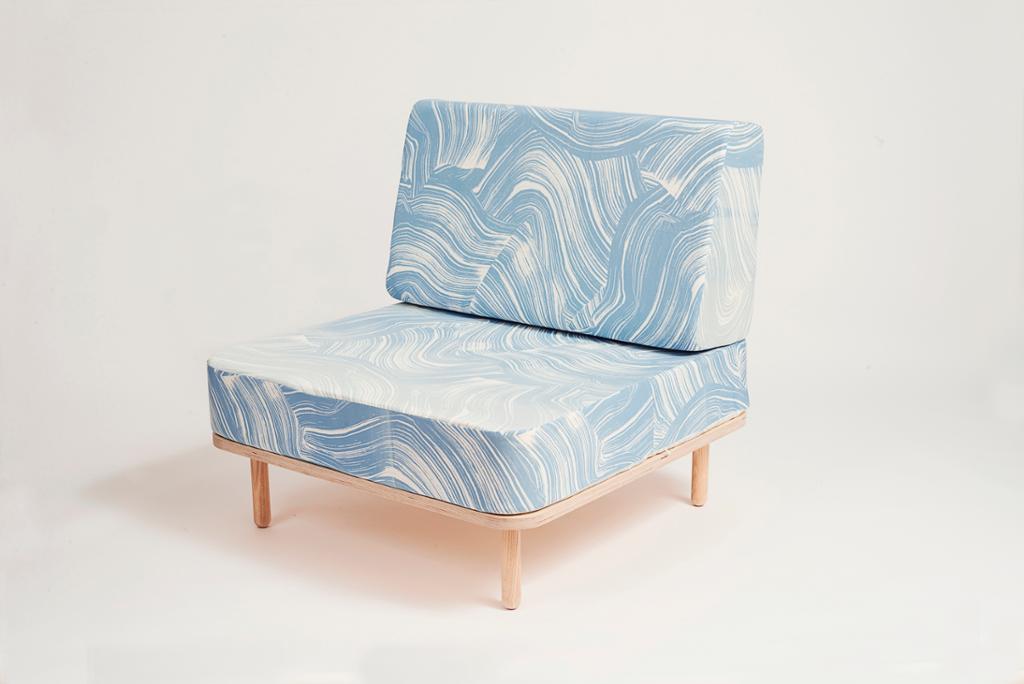 Blå og hvit stol med bein i lyst tre. Foto.