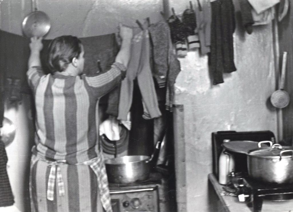 Arbeiderhusmor henger opp klesvask til tørk på kjøkkenet. Foto.