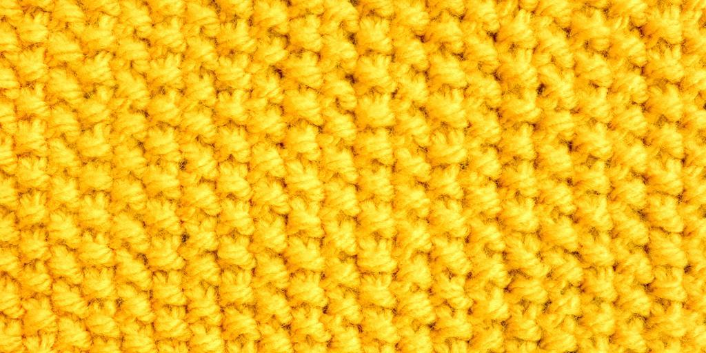 Nærbilde av gult perlestrikk. Foto.