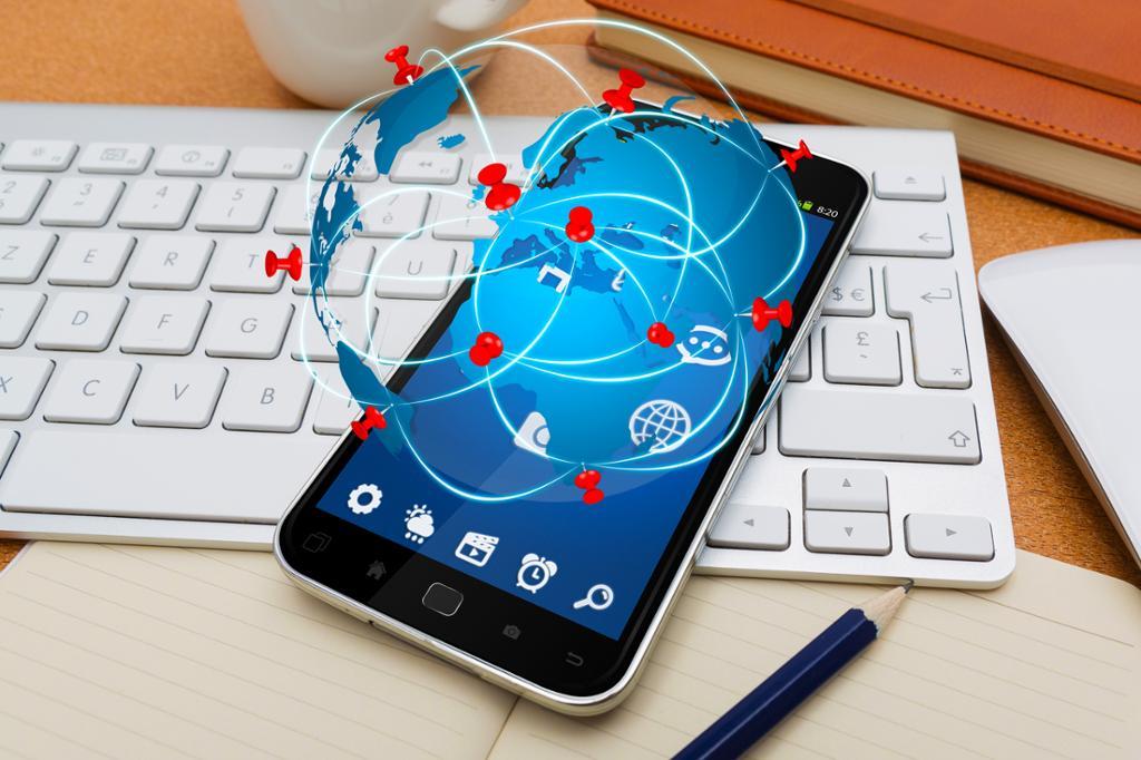 Moderne mobiltelefon på tastatur med reiseikonikoner som flyr over. Foto.