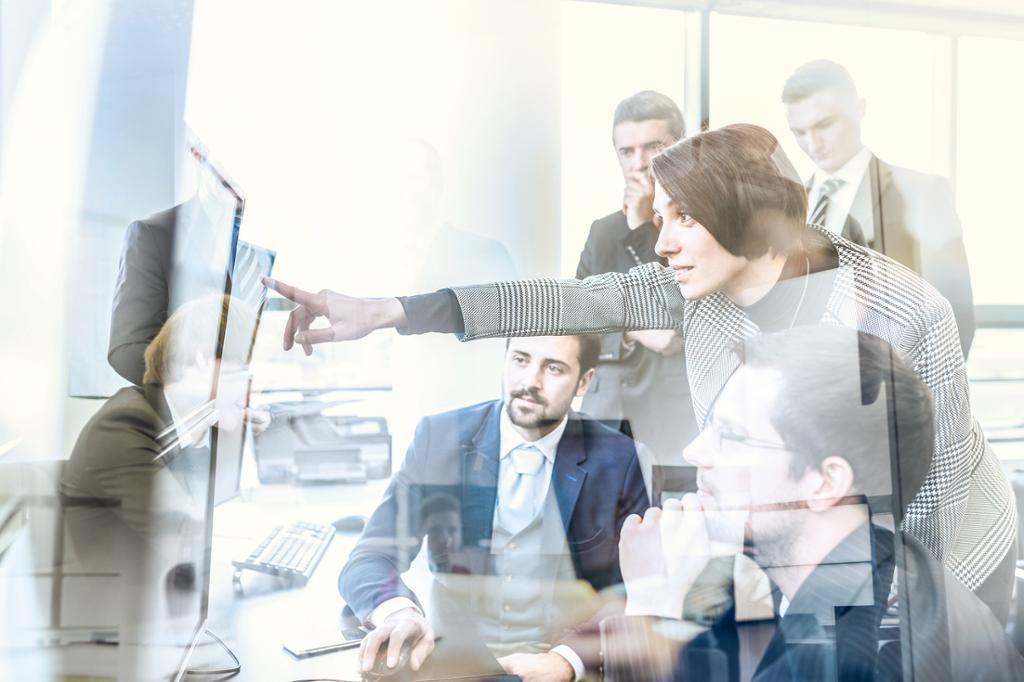 Forretningsteam ser på data på flere dataskjermer samtidig. Foto.
