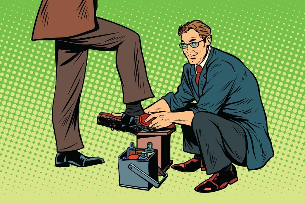 Forretningsmann får skoene sine pusset av en skopusser. Foto.