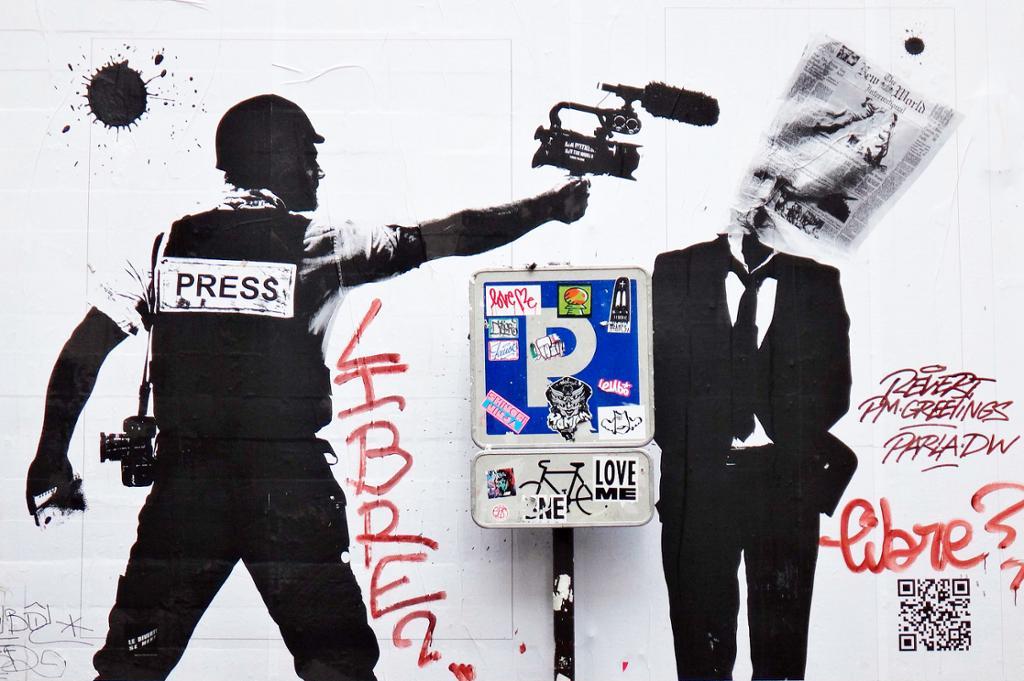 Grafitti av en pressemann skyter en avis på en dresskledd mann med videokamera. Foto.