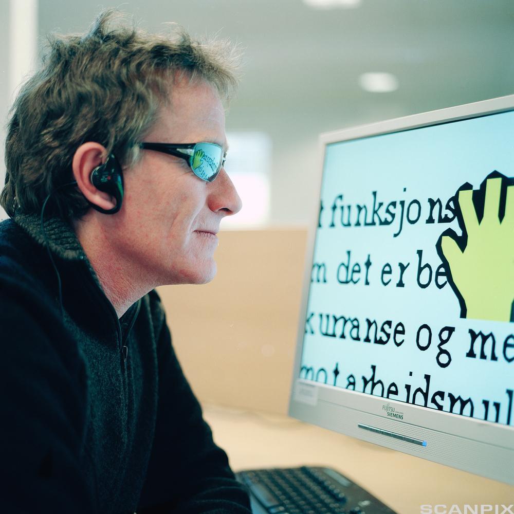 Mann foran skjerm med stor skrift. Foto.