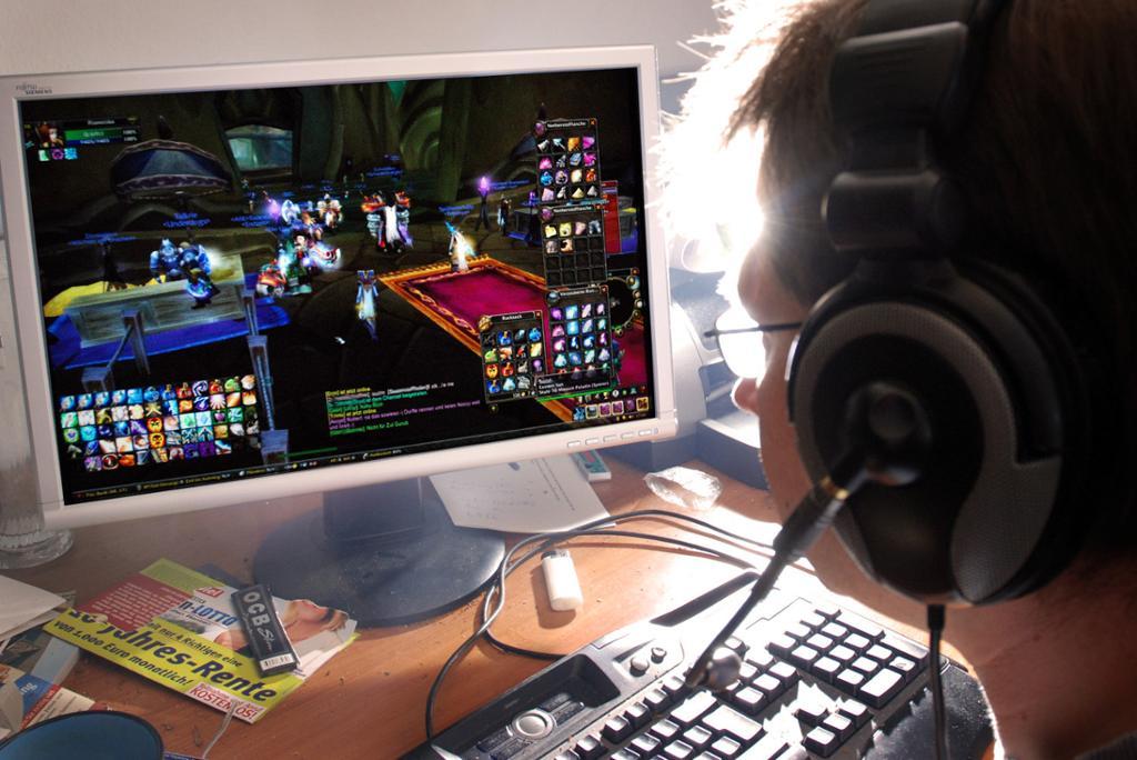 Ung mann sitter foran en stor dataskjerm og spiller videospill. Foto.