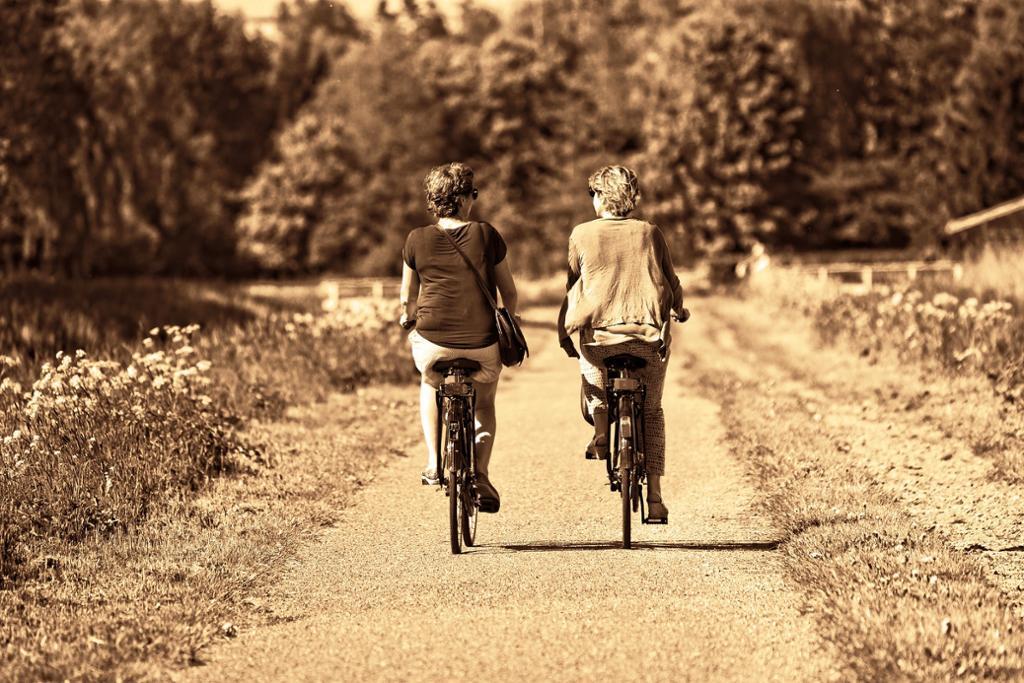 To damer sykler uten sykkelhjelm.foto.