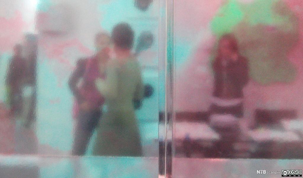 Mennesker sett gjennom et glassvindu. Foto.