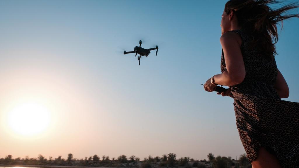 Kvinne flyr en drone. Bilde.