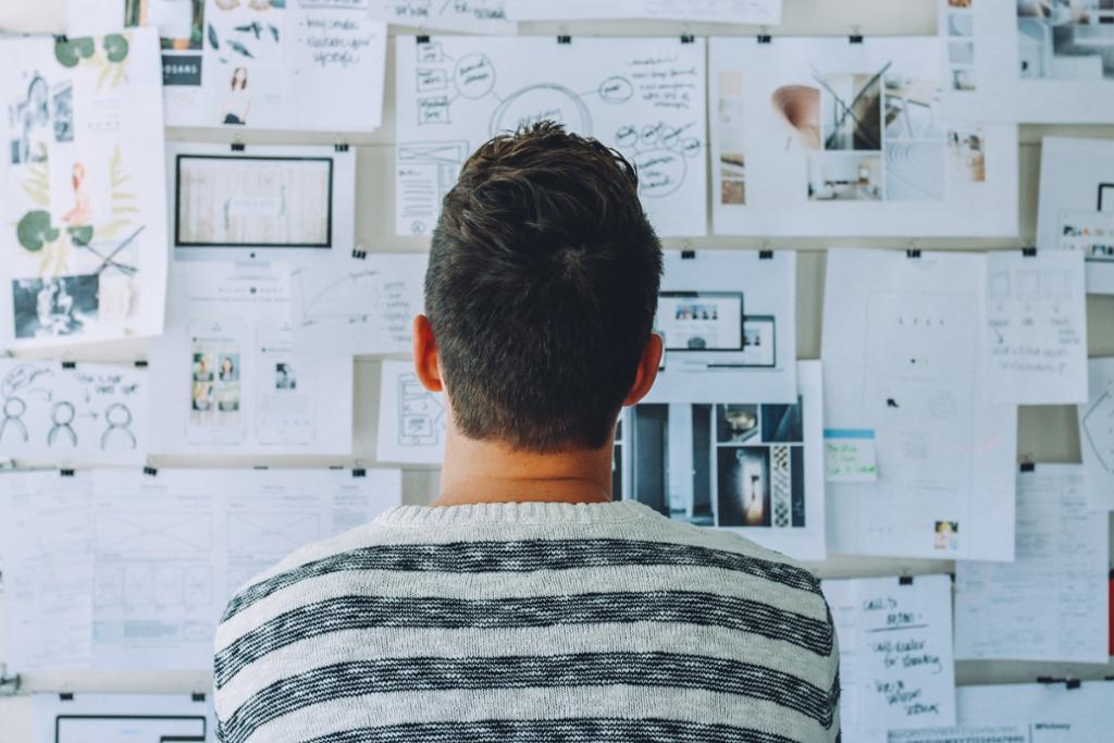 Person står med ryggen til og studerer et moodboard. Foto.
