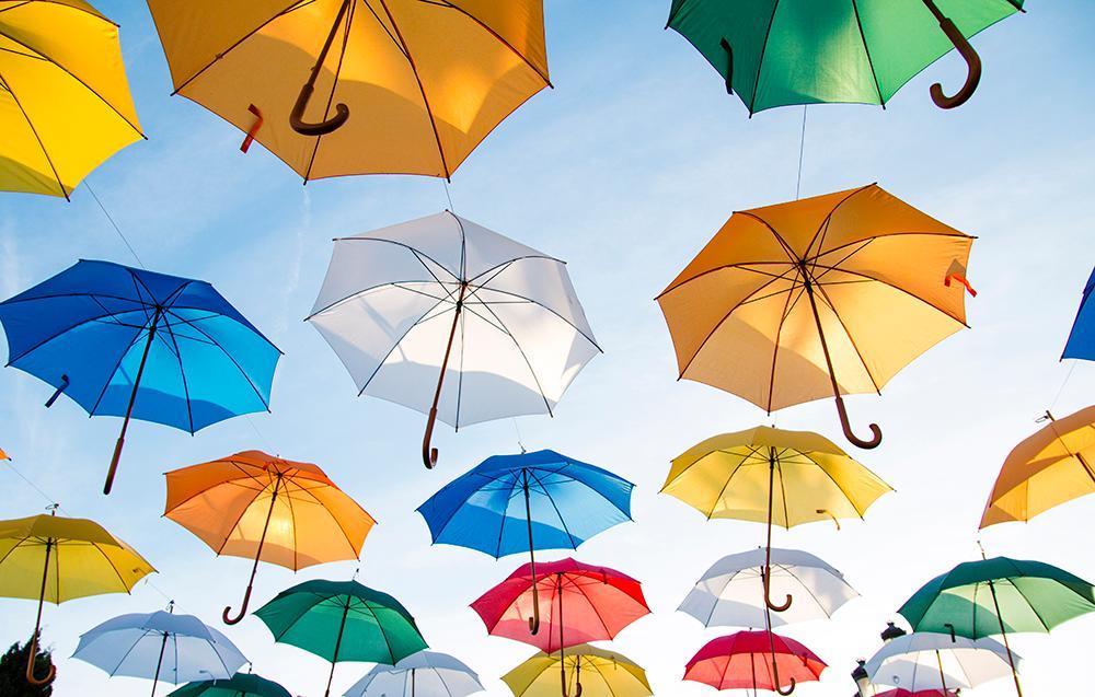 Mange fargerike paraplyer svever under himmelen. Fotografi.