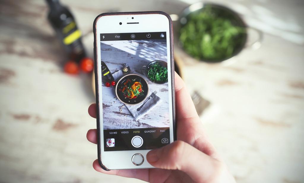 En person tar bilde av noen matretter med en iphone. Foto.
