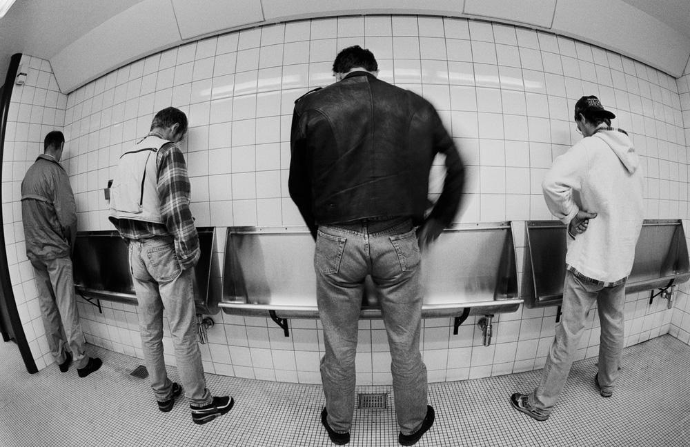 Menn som står å tisser på offentlig toalett. Foto.