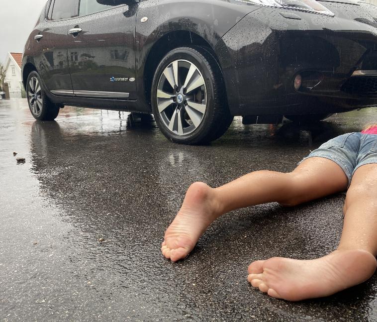 Ei jente ligger på magen på asfalten foran en bil, overkroppen er utenfor bildet. Beina ligger litt vridd. Hun er kledd i shorts, men det regner. Foto.