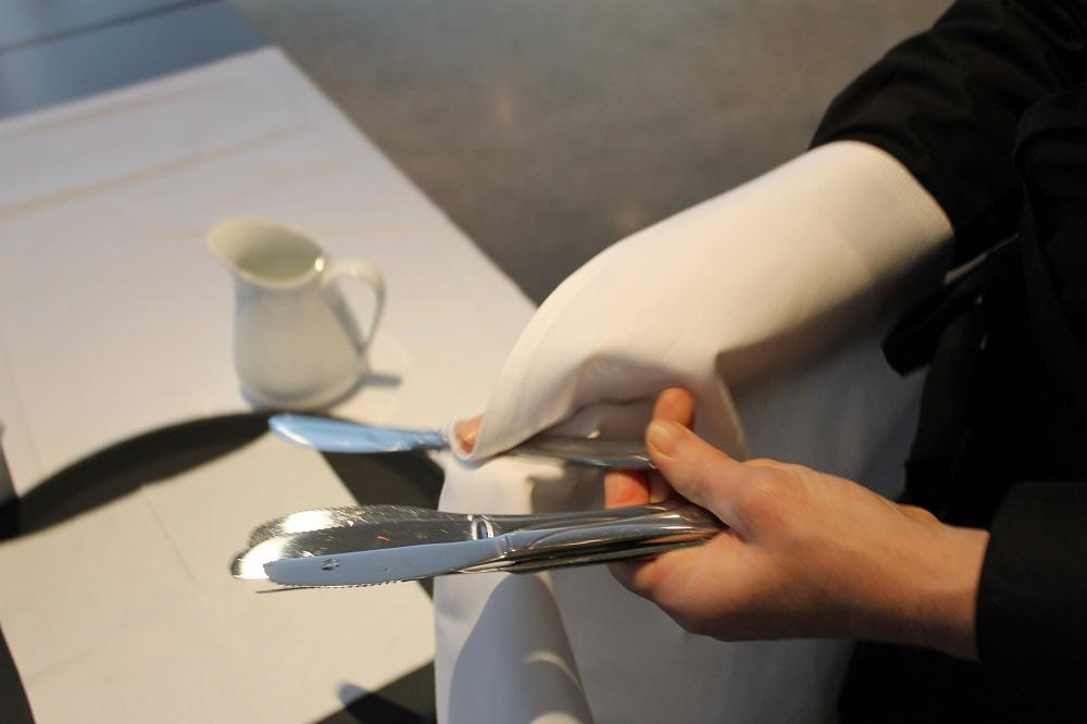 Servitør polerer knivar med ein kvit klut. Foto.