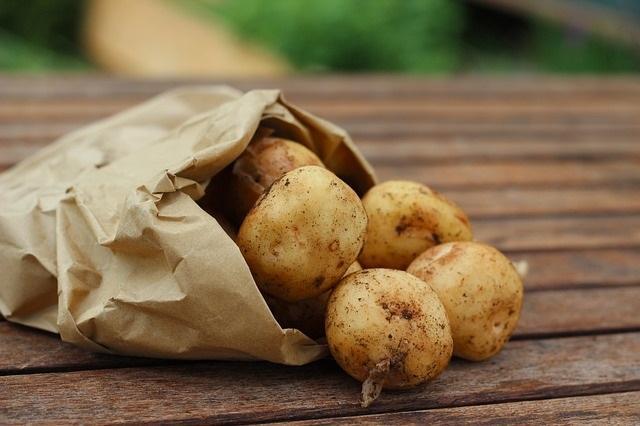 Uvaska poteter i ein papirpose. Foto.