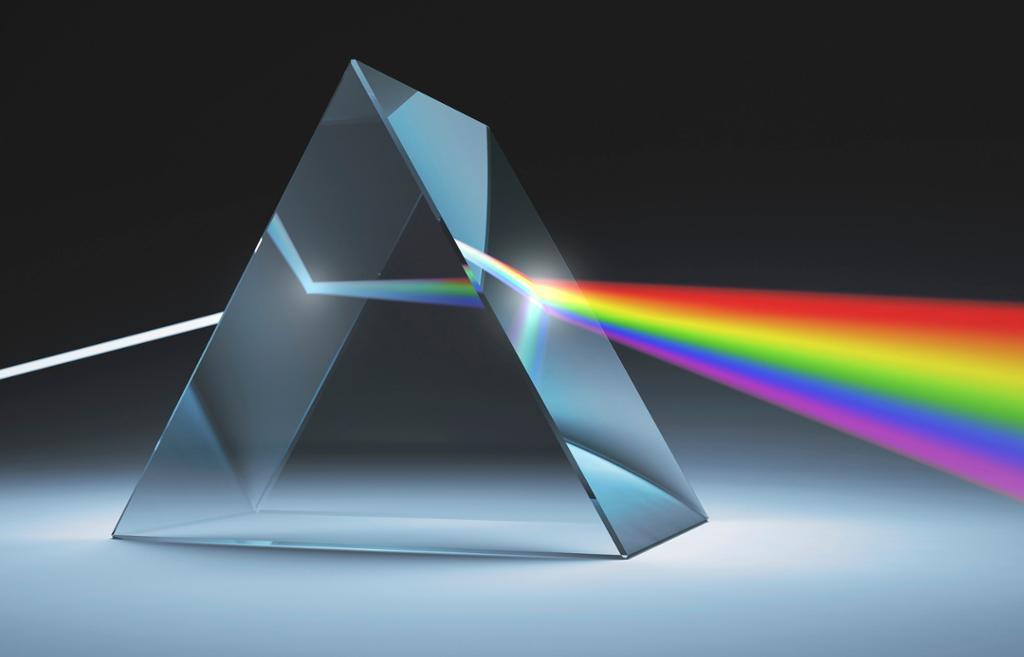 En lysstråle brytes i regnbuens farger gjennom et glassprisme. Foto.