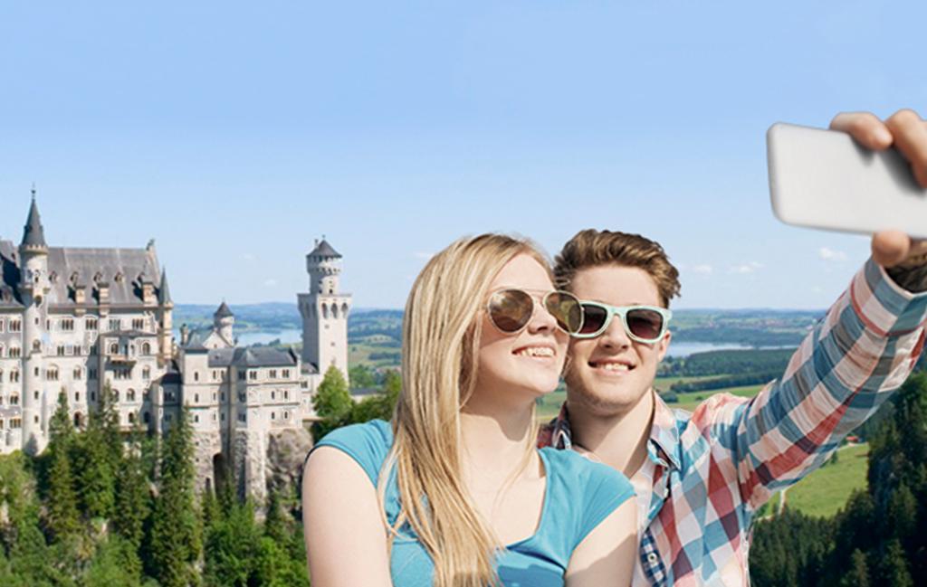 Bilde som viser to unge som tar en selfie foran slottet Neuschwanstein. Foto.