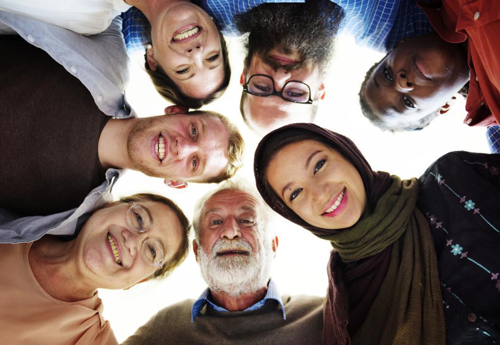 Sju personar frå ulike aldersgrupper, kjønn og etniske bakgrunnar står med hovuda saman og kikkar ned på fotografen. Foto.