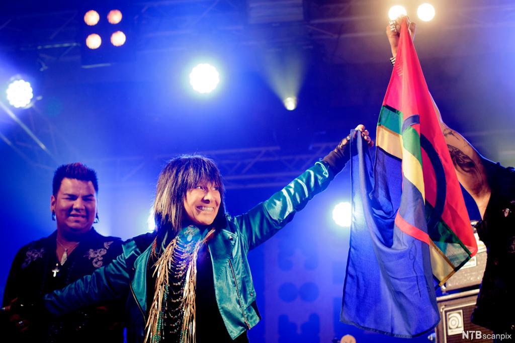 Artisten Buffy Sainte-Marie holder det samiske flagget i hånden på en scene. Foto.