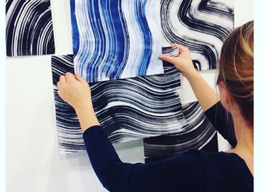 Designer vurderer ulike tekstiltrykk med bølgede linjer i blått, hvitt og svart. Hun holder dem opp mot veggen. Foto.