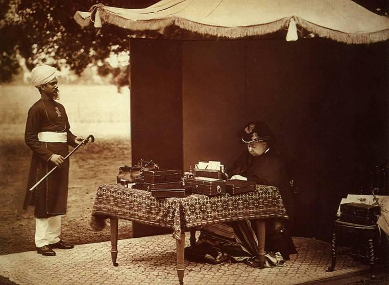 Dronning Victoria og hennes indiske tjener Abdul Karim. Dronningen sitter og arbeider ved et bord under et åpent telt. Foto.