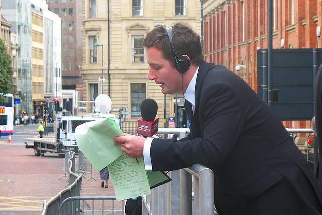 Mann i bymiljø som snakker i mikrofon med hodetelefoner på ørene og papirer i hendene. Foto.