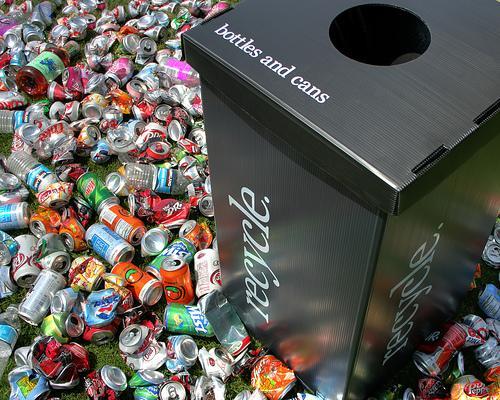 En søppelkasse oppå et berg med drikkeflasker. Foto.