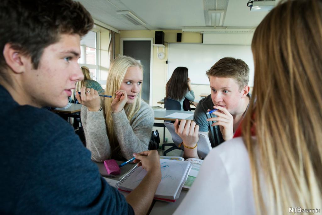 Elever i eit klasserom snakker saman i ein liten gruppe. Foto.