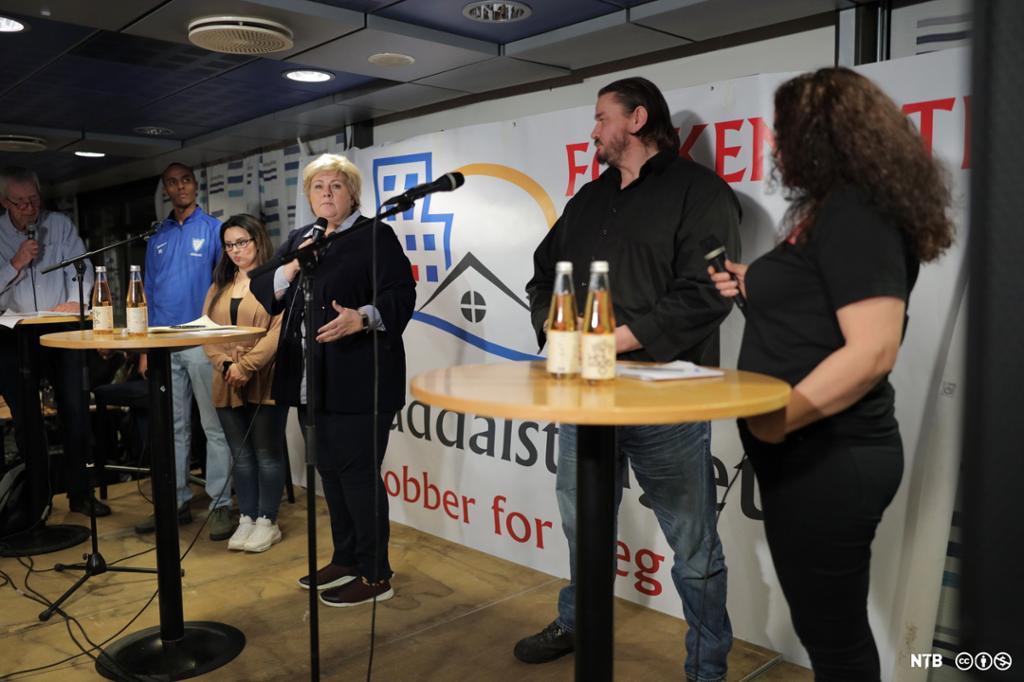 Statsminister Erna Solberg snakkar på eit podium med fire andre deltakarar på Groruddalstinget.