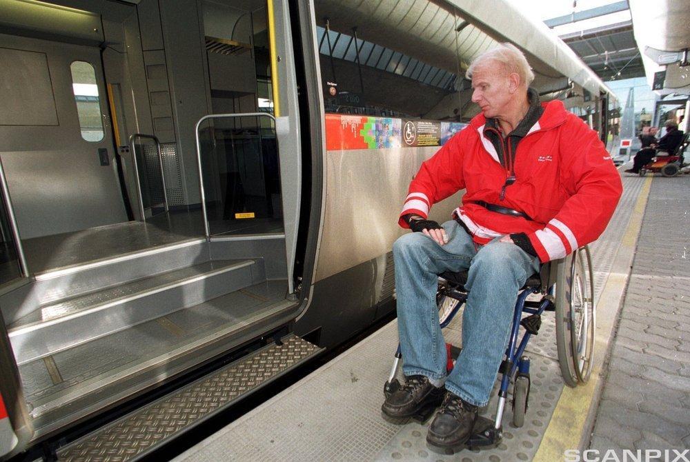 Mann i rullestol ved tog utan universell utforming. Foto.