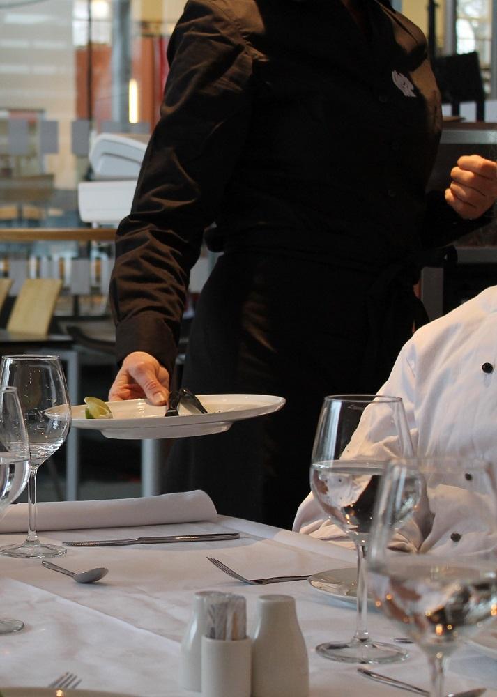 En servitør som rydder av middagstallerkenen. Foto.