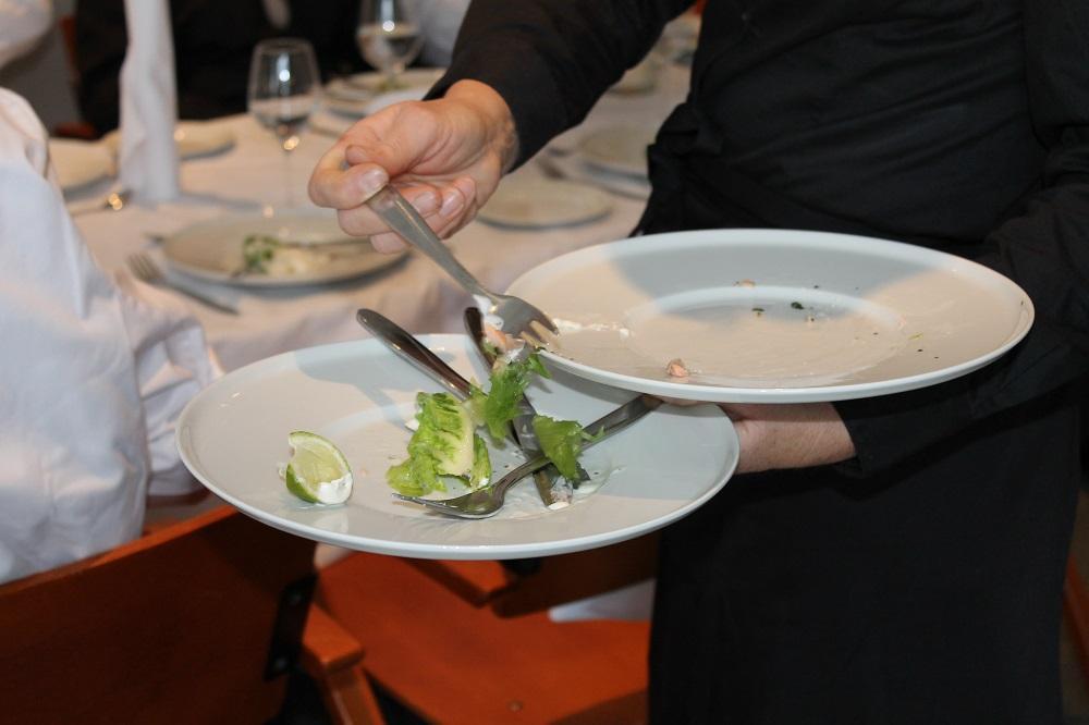 Servitør ryddar av bord i ein restaurant. Foto.