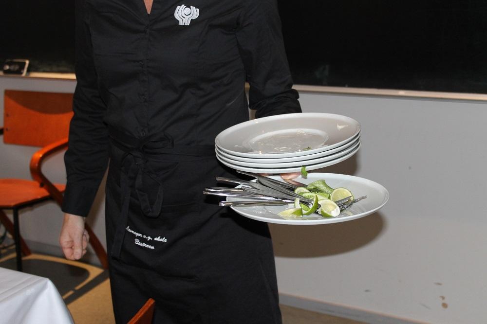 Servitør rydder av bord i en restaurant. Foto.