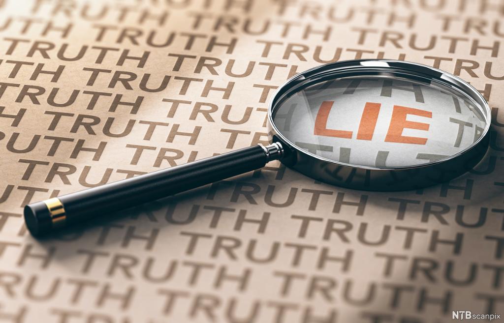 Et forstørrelsesglass ligger over ordet lie, på en side der det står truth mange ganger.  Foto.