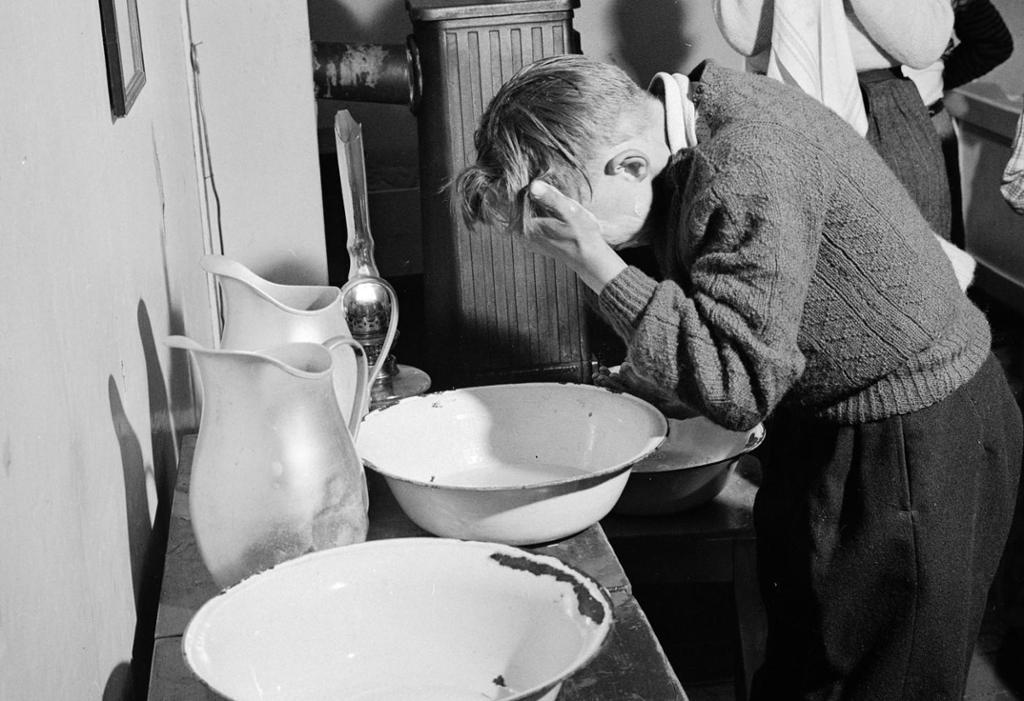 To gutter vasker seg med vaskevannsfat og klut. Foto.