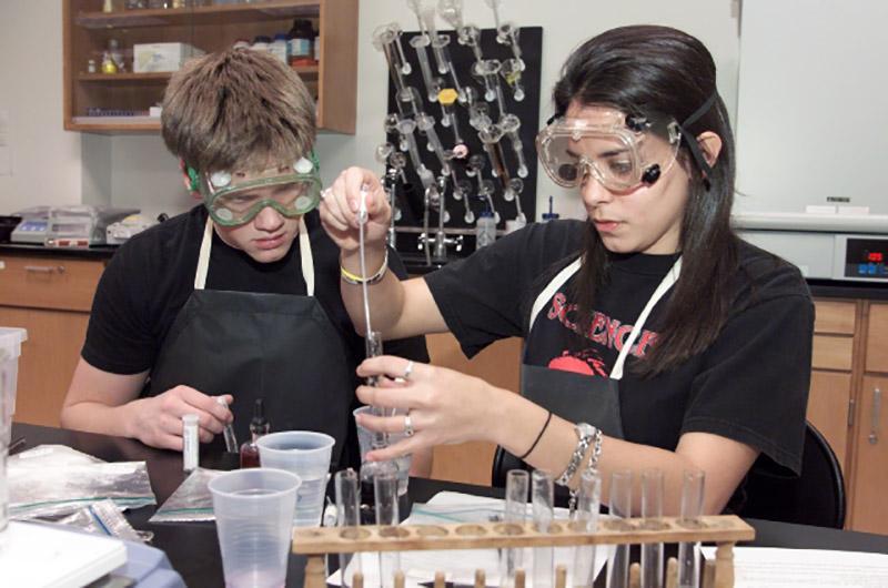 En gutt og jente arbeider på laboratorium med vernebriller. Foto.