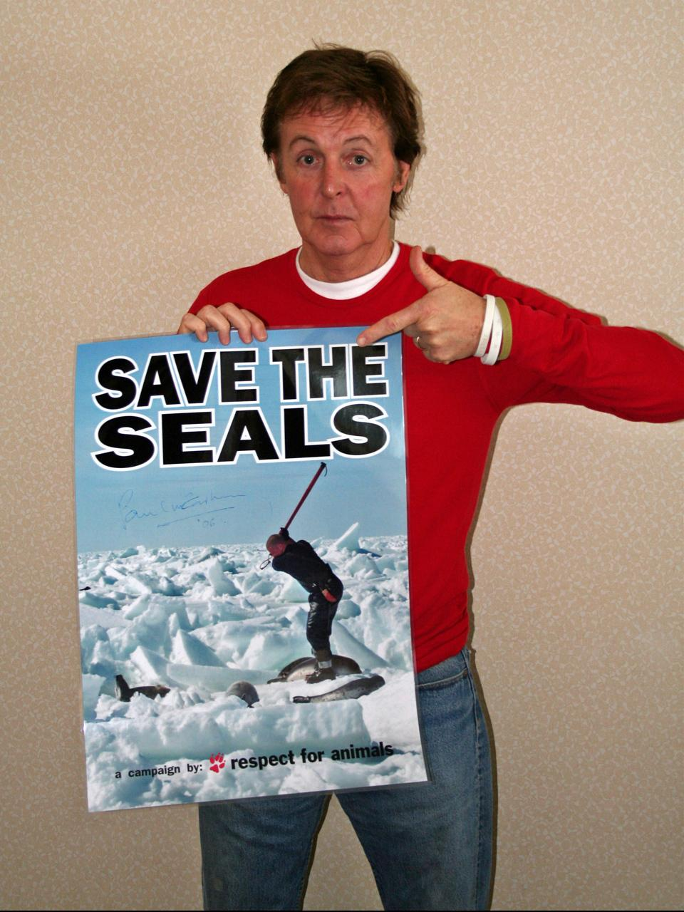 "Paul McCartney holding the poster ""save the seals"". Photo."