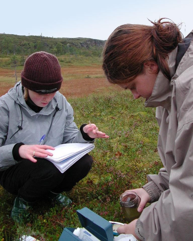 To jenter skriver notater og tar målinger under feltarbeidet. Foto.