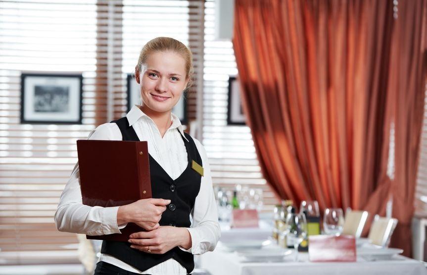 En kvinnelig servitør holder en meny foran et bord. Foto.