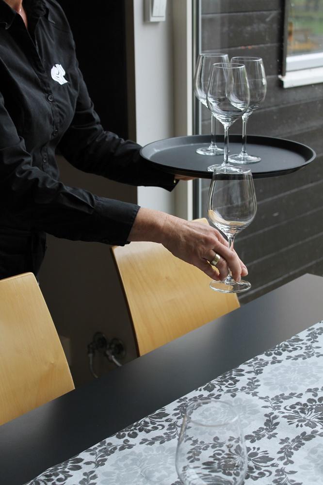 Servitør demonstrerer bæreteknikk for glass. Foto.