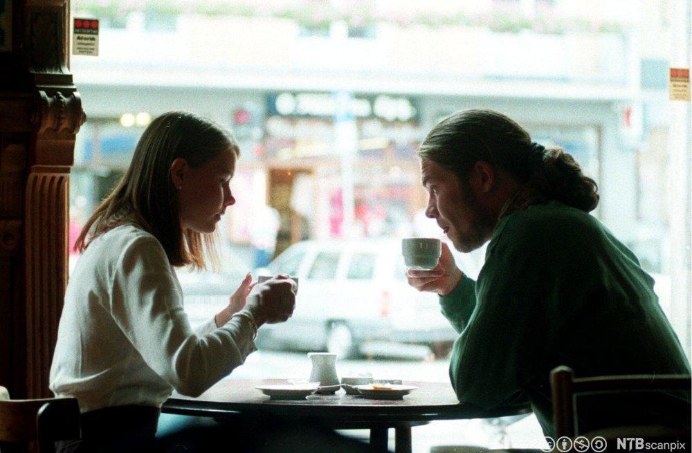 En ung mann og dame nyter en kopp kaffe på en kafe`. Foto