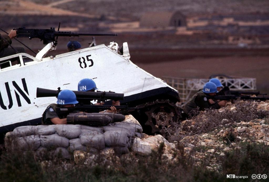 FN-soldater med skytevåpen bak sandsekker ved siden av armert kjøretøy. Foto.