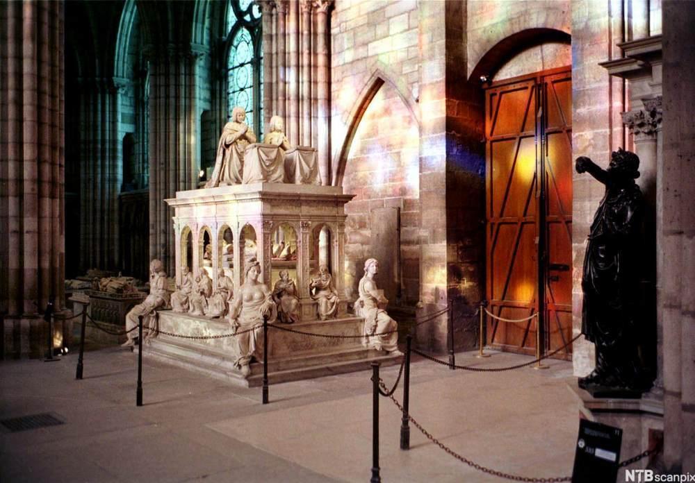 Gravmonument med statuar sitjande oppå og rundt inne i ei kyrkje.