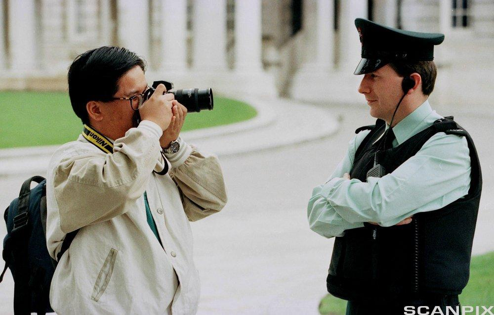 A tourist photographs a Royal Ulster Constabulary officer in Belfast