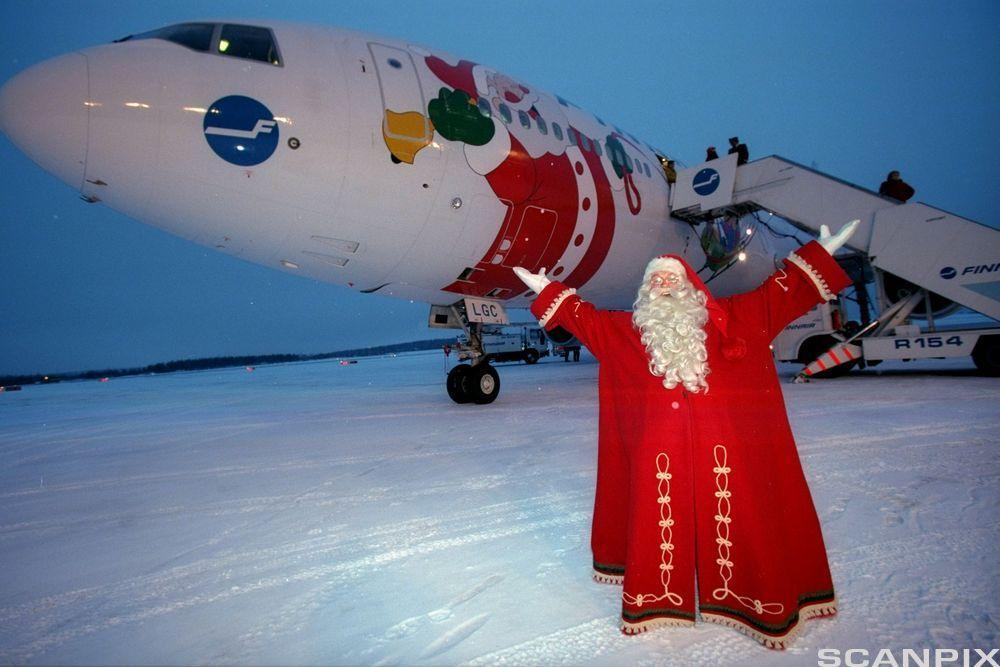 En julenisse hilser flypassasjerer velkommen når de kommer ut av flyet. Foto.