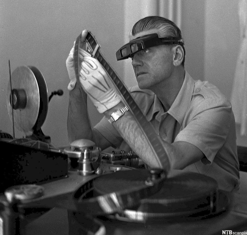 Filmregissør Tancred Ibsen sit ved klippebordet og studerer ein film frå rull. Foto.