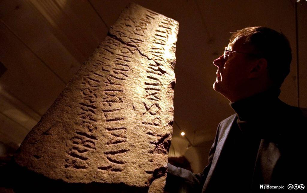 Mann studerer stein med runer. Foto.