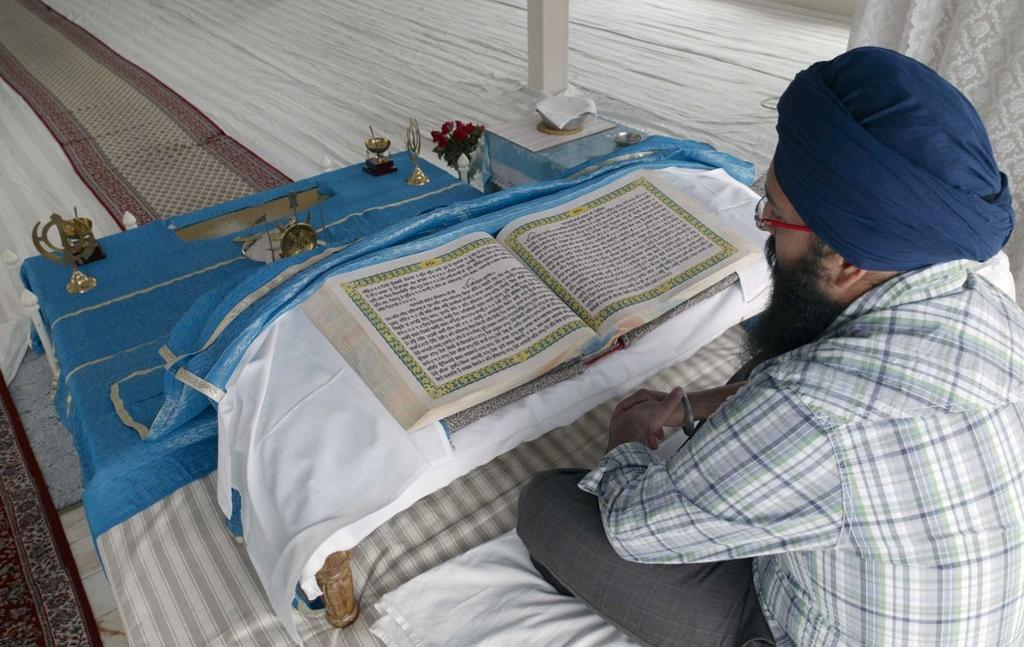 En mann med turban foran en oppslått bok som ligger på et hvitt klede. Foto