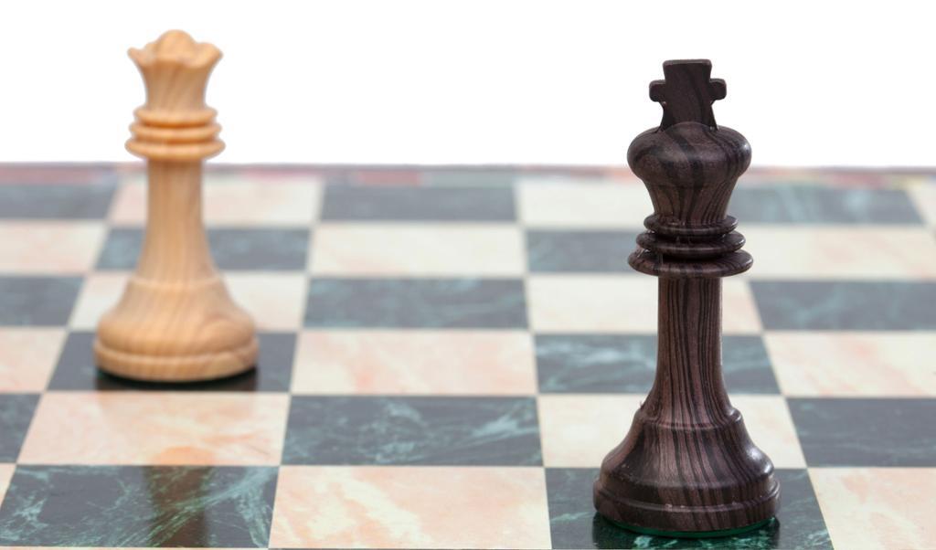 Sjakkbrett med svart konge og hvir dronning. Foto.