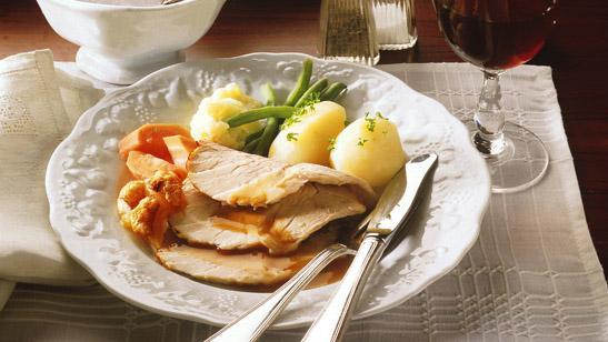 Tallerken med svinestek, potet og diverse grønnsaker. Foto.